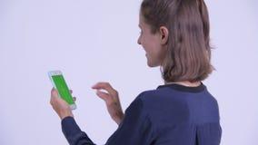 Bakre sikt för Closeup av den lyckliga unga affärskvinnan som använder telefonen stock video