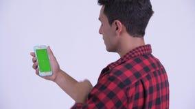 Bakre sikt för Closeup av den lyckliga unga latinamerikanska hipstermannen som använder telefonen arkivfilmer