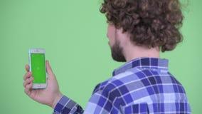 Bakre sikt för Closeup av den lyckliga unga skäggiga hipstermannen som använder telefonen lager videofilmer