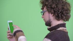 Bakre sikt för Closeup av den lyckliga unga skäggiga mannen som använder telefonen arkivfilmer