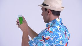 Bakre sikt för Closeup av den unga lyckliga latinamerikanska turist- mannen som använder telefonen lager videofilmer