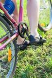 Bakre sikt för närbild av fot av den Caucasian cyklisten på cirkulering royaltyfri fotografi
