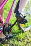 Bakre sikt för närbild av fot på cykelpedalen royaltyfria bilder