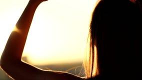 Bakre sikt för närbild av rörande hår för ung kvinna på balkongen på solnedgången stock video