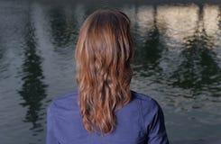 Bakre sikt för röda haired kvinnor Hon ser sikt in Arkivfoton