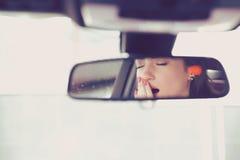 Bakre spegelsikt av en sömnig gäspa kvinna som kör hennes bil efter drev för lång timme Arkivfoton