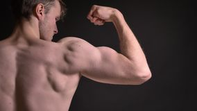 Bakre stående för närbild av den unga caucasian mannen som visar hans muskulösa biceps och visar hans makt på svart arkivfilmer