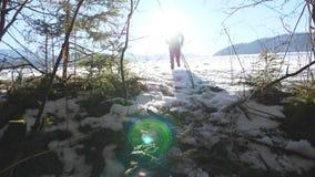 Bakre tillbaka sikt av den oigenkännliga mannen som joggar på snöig fält nära den unga fotvandraren för skog som kör på snöäng på stock video