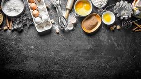 Bakselachtergrond Bloem met cacao, eieren en bakselvormen van het deeg stock foto's