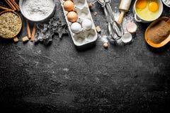 Bakselachtergrond Bloem met cacao, eieren en bakselvormen van het deeg royalty-vrije stock fotografie
