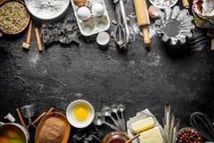 Bakselachtergrond Bloem met cacao, eieren en bakselvormen van het deeg stock afbeeldingen