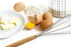 Bakselingrediënten voor pannekoeken, boter, eieren, bloem, melk en a Royalty-vrije Stock Afbeeldingen