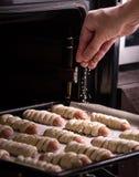 Bakseloven: de bakker bestrooit broodjes met sesamzaden vóór het bakken in de oven Royalty-vrije Stock Afbeelding