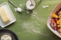 Bakselwerktuigen, bloem, suiker, boter op groene houten oppervlakte Royalty-vrije Stock Fotografie