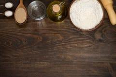 Bakselwerktuigen en ingrediënten voor pizzadeeg op houten achtergrond Stock Foto's