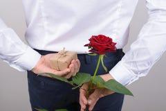Baksida bak fotoet för den bakre sikten av den lyckliga romantiska charmiga stiliga gentlemannen som döljer den härliga rosen och arkivfoto