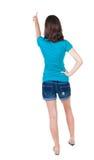 Baksida beskådar av att peka kvinnan härlig brunettflicka i kortslutningar Arkivfoton