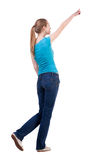 Baksida beskådar av gå kvinna, i jeans och att peka för skjorta Royaltyfri Fotografi