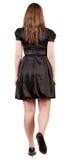 Baksida beskådar av gående brunettkvinna i svart klänning. Royaltyfria Bilder