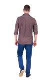 Baksida beskådar av gående stilig man i jeans och en skjorta Royaltyfria Bilder