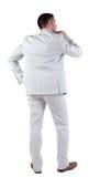 Baksida beskådar av tänkande ung affärsman i vit passar. Royaltyfri Foto