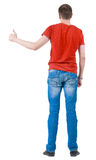 Baksida beskådar av unga manar i orange t-skjorta gående tum upp. fotografering för bildbyråer