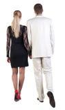 Baksida beskådar av gående ung affär kopplar ihop (manen och kvinnan). Arkivfoto