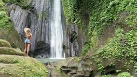 Baksida för flyg- sikt av kvinnan som ser den härliga vattenfallet i grön tropisk regnskog i Bali stock video