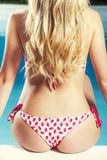 Baksida och ung blond kvinna för bakdelar i baddräktsammanträdepoolside Royaltyfria Bilder