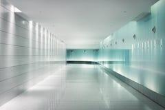 Baksida-tände glasväggar i en underjordisk futuristic korridor Arkivfoto