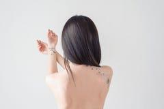 Baksidan av en flicka med en tatuering Royaltyfri Foto