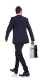 Baksidt av en gå affärsman som rymmer en portfölj Royaltyfri Bild