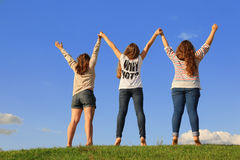 Baksidt av tre flickor som rymmer händer på gräs Royaltyfri Foto