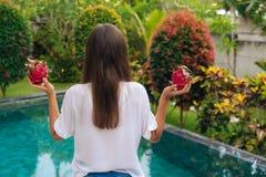 Baksikt av det spensliga flickaanseendet med drakefrukter, pitaya nära pöl i härlig trädgård royaltyfri fotografi