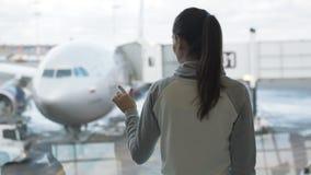 Baksiktsflickan ser nivån i flygplatsfönster- och attraktionhjärtatecken arkivfilmer