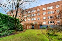 Baksteen groot oud flatgebouw met groene de lentebinnenplaats. Stock Afbeeldingen