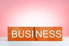 Baksteen met barst-symbool gebroken schade, onderbreking van zaken op roze achtergrond Bedrijfs concept stock fotografie