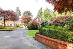 Baksteen rood huis met Engelse tuin en witte vensterblinden en oprijlaan. Stock Afbeeldingen