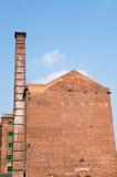 Baksteenfabriek en schoorsteen tegen een blauwe hemel Stock Fotografie