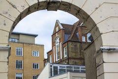 Baksteenhuis op verscheidene niveaus met grote mooie vensters Beeld door de oude boog wordt genomen die De Horizon van Londen royalty-vrije stock foto's