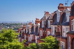 Baksteenhuizen van Muswell-Heuvel en panorama van Londen met Canary Wharf, Londen, het UK stock afbeelding