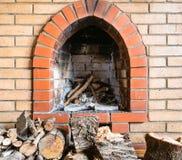 Baksteenopen haard en firewoods in het dorpshuis stock foto