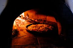 Baksteenoven met hete pizza die binnen koken Stock Afbeelding