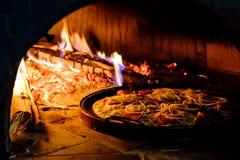 Baksteenoven met hete pizza die binnen koken Stock Foto's