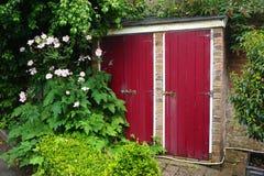 Baksteentuin met heldere rode deuren wordt afgeworpen die Stock Foto's