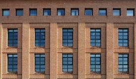 Baksteenvoorgevel van een modern gebouw met brede vensters en een rij van kleine vierkante vensters bij de bovenkant Royalty-vrije Stock Foto
