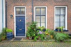 Baksteenvoorgevel van Oud Nederlands Huis met bloemen in potten Stock Fotografie
