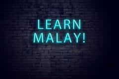Bakstenen muur en neonteken met inschrijving Malay concept het leren stock foto's