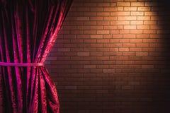 Bakstenen muur en rood gordijn stock afbeeldingen