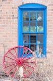 Bakstenen muur met blauw venster en rood wagenwiel stock afbeeldingen